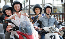 Young and mature couples driving petrol scooters Royalty Free Stock Photography