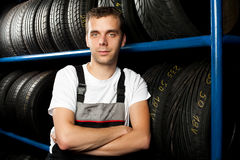 Young mechanic. Portrait of  young mechanic standing next to tire shelves in tire store Royalty Free Stock Photos