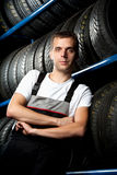 Young mechanic. Standing next to tire shelves Royalty Free Stock Images