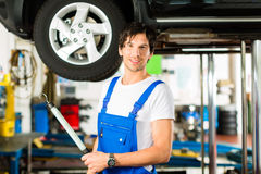 Young mechanic in blue overall working on car. Young man in blue overall - mechanic - working with lamp on jacked car in a service station Stock Image