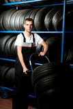 Young mechanic carrying tire in car service. Portrait of  young mechanic carrying tire in car service Royalty Free Stock Image