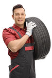 Young mechanic carrying a tire and looking at the camera Royalty Free Stock Image