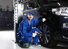 Young mechanic changing wheel service. Young mechanic changing wheel in car service Stock Photo
