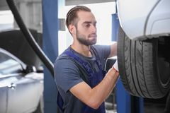 Young mechanic changing wheel. At tire service Stock Photo