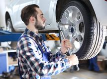 Young mechanic changing wheel. At tire service Royalty Free Stock Photos