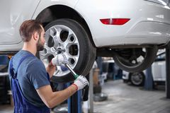 Young mechanic changing wheel. At tire service Stock Photography