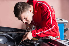 Young mechanic checking the oil level in a car engine Stock Photos