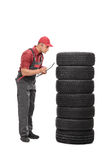Young mechanic checking quality of tires Royalty Free Stock Image