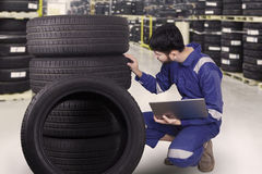 Young mechanic checks a pile of tires. Portrait of young technician working with laptop and check a stack of tires in the workshop Stock Image