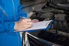 Young mechanic engineer taking a note on clipboard for examining. A vehicle Stock Photos