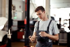 A young mechanic is focused on filling in a form stock images