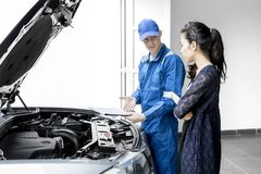 Young mechanic giving repair cost to his client Royalty Free Stock Photography