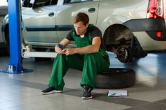 A young mechanic in a green overalls sits on a wheel in service.  royalty free stock photos