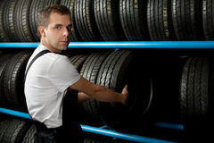 Young Mechanic holding a car tire. In car service Royalty Free Stock Image