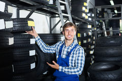 Young mechanic man working with car tires in workshop Stock Photo
