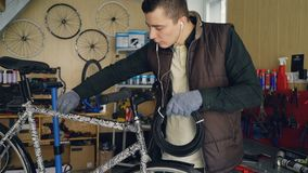 Young mechanic owner of bike repairing workshop is fixing bicycle holding bundle of wire and fixing it to bike frame. Young mechanic owner of bike repairing stock footage