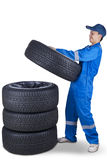 Young mechanic pile up tires. Portrait of male technician with a blue uniform and pile up four black tires, isolated on white Stock Photo