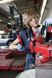 Young mechanic in protective clothing concentrating on repairing machine part in garage Royalty Free Stock Photos