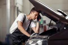 A young mechanic is puzzled while working at a car service and maintenance stock images