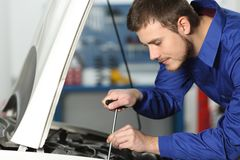Mechanic repairing a car in a workshop. Young mechanic repairing a car in a mechanical workshop stock image