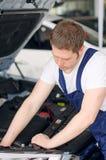 Young mechanic repairing car. Royalty Free Stock Photo