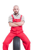 Young mechanic with serious face sitting on car wheel stock images