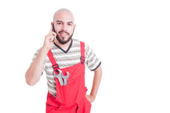 Young  mechanic talking on the phone looking happy Royalty Free Stock Photography