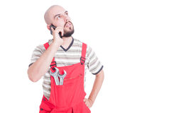 Young  mechanic talking on the phone looking up Stock Image