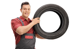 Young mechanic with a tire looking at the camera Royalty Free Stock Photography
