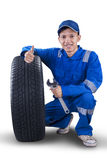 Young mechanic with tire showing thumb up Royalty Free Stock Images