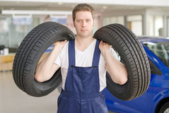 Young mechanic with tires. Royalty Free Stock Images