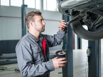 Young mechanic with a tool in hand replacing a car tire. Close-up of a mechanic with a wheel. Concept work, machines stock photos