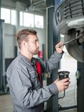 Young mechanic with a tool in hand replacing a car tire. Close-up of a mechanic with a wheel. Concept work, machines stock photography