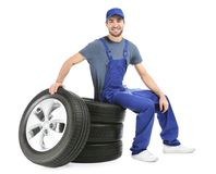Young mechanic in uniform with car tires. On white background Stock Image