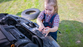 Young mechanic at work on a beautiful sunny summer day. Girl repairing car on the sunny green glade stock video footage