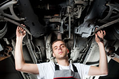 Young Mechanic working below car in uniform Stock Photography