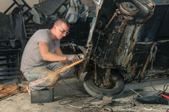 Young mechanical worker repairing an old vintage car Stock Photography