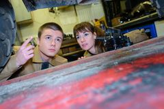 Young mechanics looking at underneath vehicle. Young mechanics looking at underneath of vehicle Stock Image