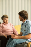 Young medic and his elderly patient Stock Photography
