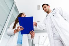 Young Medical Colleagues Analysing Data On Paperboard. At Hospital Indoor stock image