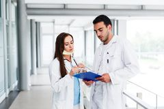 Young Medical Colleagues Analysing Data On Paperboard. At Hospital Indoor stock images