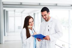 Young Medical Colleagues Analysing Data On Paperboard. At Hospital Indoor royalty free stock photography