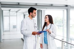 Young Medical Colleagues Analysing Data On Paperboard. At Hospital Indoor royalty free stock photo