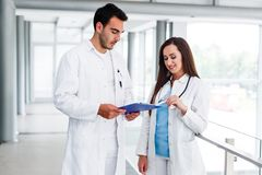 Young Medical Colleagues Analysing Data On Paperboard. At Hospital Indoor royalty free stock images