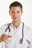 Young medical doctor man with stethoscope showing a glass of water. Royalty Free Stock Images