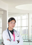Young Medical Professional in Clinic. Young female medical professional wearing scrubs and lab coat in modern clinic setting. Woman has a serious expression with Royalty Free Stock Image