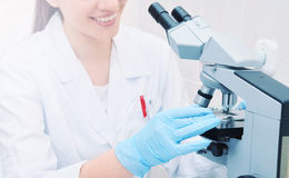 Young medical researcher looking through microscope in laborator. Young woman medical researcher looking through microscope in laboratory, medicine concept Royalty Free Stock Photos