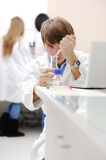 Young medical scientist working in modern lab. Research with tubes and notebook Stock Photography