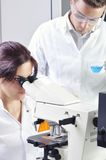 Young medical scientists studying new substance or virus in microscope Stock Photo