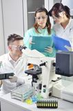 Young medical scientists studying new substance or virus with microscope Stock Photos